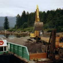 Material barge with excavator unloading aggregate