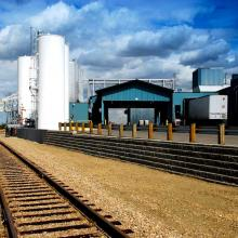 Railway Tracks in front of chemical storage tanks and truck canopy