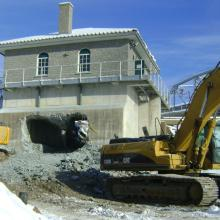 Excavators in front of building with large hole in foundation