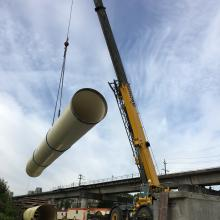 large process pipe being lifted by crane