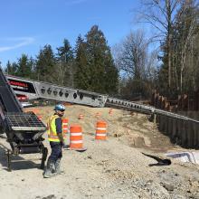 concrete pump truck arm pouring into deep excavation