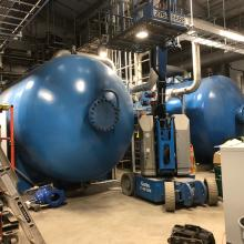 Genie lift next to two large boilers