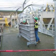Installers moving Slide Gates for tank
