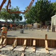 Pump truck next to formwork for building addition slab pour